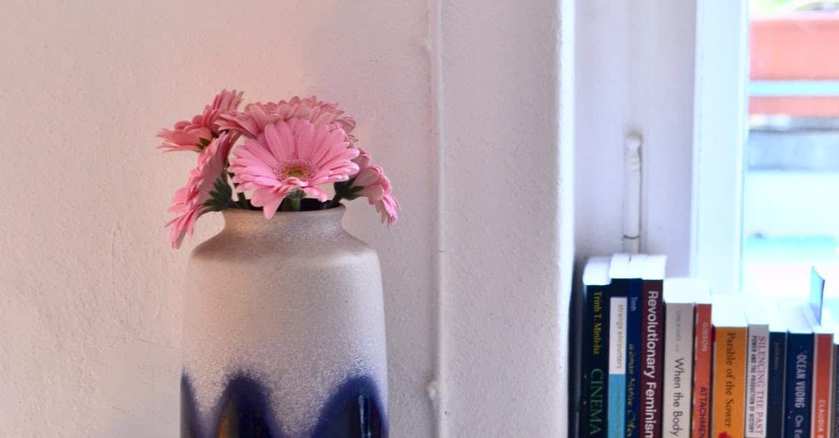 A vase filled with pink flowers sitting on top of a book shelf