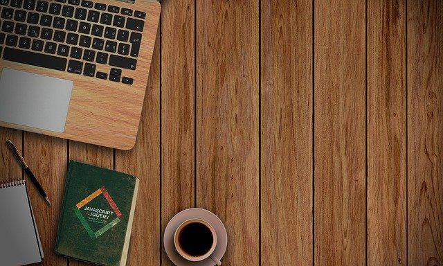 A laptop computer sitting on top of a wooden table